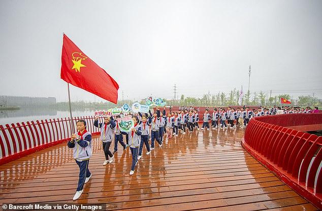 Decenas de millones de libras esterlinas en ayuda exterior aún pueden ir a China a pesar de la promesa de recortar los fondos a la superpotencia mundial.  Los ministerios de Whitehall, incluido el departamento comercial, no estarán cubiertos por la nueva represión del flujo de efectivo a Beijing.  En la imagen: los niños participan en un desfile del Día de la Tierra en Suqian, China
