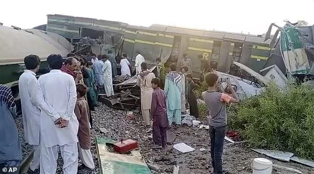 Los rescatistas y los aldeanos locales en el lugar de los hechos esta mañana mientras los vagones de tren yacen lateralmente fuera de la vía en el distrito Ghotki de la provincia de Sindh el lunes.  Al menos 35 personas han muerto en los trenes que transportaban un total de 1.100 pasajeros.