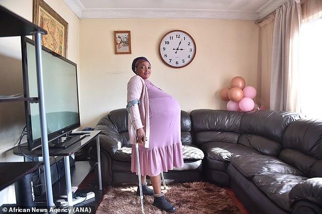 Gosiame Sithole, exgerente de tienda, posa en su sala de estar en Pretoria antes del nacimiento