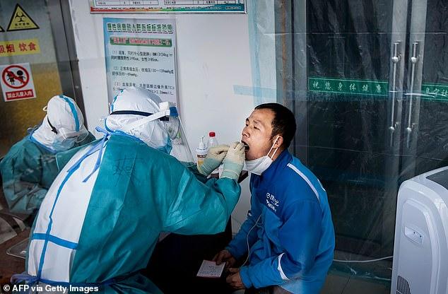 Esta foto tomada el 24 de abril de 2020 muestra al personal médico tomando muestras de un hombre como parte de las medidas pandémicas de COVID-19, en un centro de servicios de salud en Suifenhe, en la provincia de Heilongjiang, noreste de China.