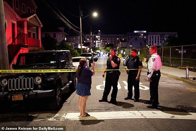 Una mujer habla con la policía en la escena de un doble tiroteo fatal cerca de 342 Beach 45th St. en Queens