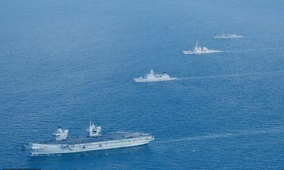 El HMS Queen Elizabeth (frente en la foto a principios de esta semana) ha llegado al Mar de China Meridional cuando Beijing amenaza con `` expulsar '' a los buques de guerra británicos si navegan cerca de las islas que reclama.