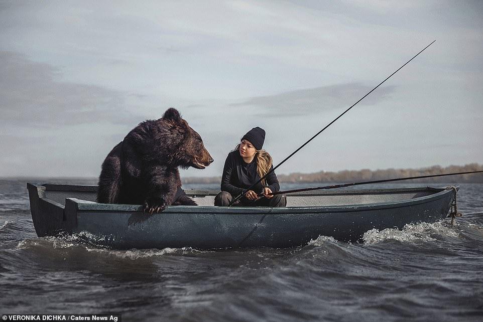 En la foto: Archie, un oso pardo rescatado, junto con su dueña Veronika Dichka pescando en un barco en Novosibirsk, Rusia.
