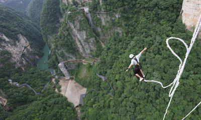 Los saltadores de puenting disfrutan de una vista aérea de la naturaleza salvaje de Wulingyuan, una popular atracción turística internacional, famosa por sus pilares y picos de arenisca de cuarcita que se extienden hacia las nubes, junto con profundos barrancos y gargantas.
