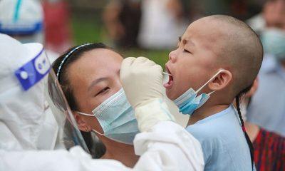 Un médico que usa equipo de protección personal completo hace un hisopado de un niño para detectar Covid en un centro de pruebas en Yangzhou, en la provincia de Jiangsu, en el este de China.  La ciudad había registrado 126 casos hasta el martes.