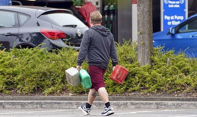Un hombre que transportaba contenedores en una gasolinera Tesco en Bracknell, Berkshire, en medio de la escasez de conductores de vehículos pesados