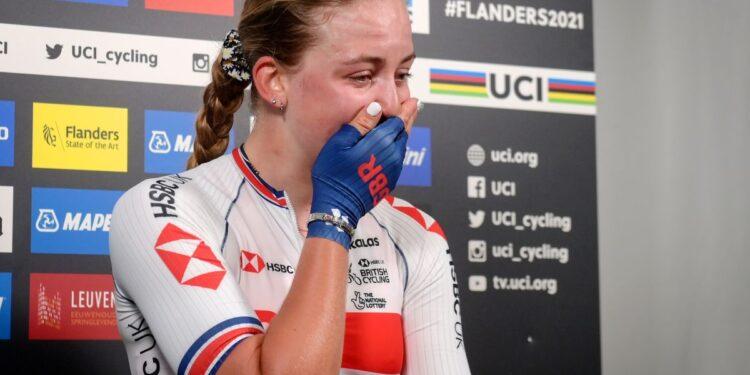 Zoe Bäckstedt mantiene la compostura hasta que la línea de meta se rompe para tomar la camiseta arcoíris mientras papá Magnus observa desde el stand.