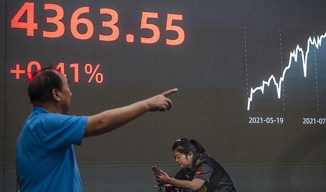 Ahora se espera que los problemas de la deuda del gigante inmobiliario chino Evergrande desaceleren drásticamente el crecimiento en la segunda economía más grande del mundo (en la foto, un hombre caminando frente a una pantalla en una bolsa de valores en Shanghai)
