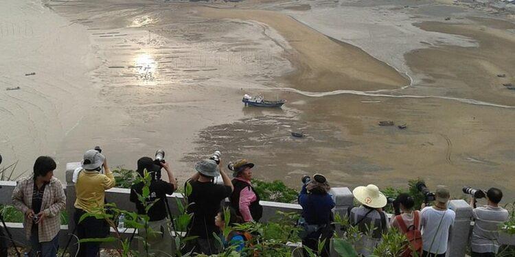 Melinda Chan visitó Xiapu, que tiene una costa en el Mar de China Oriental, y fotografió enjambres de turistas capturando a pescadores (arriba).  En declaraciones a MailOnline Travel, dijo: 'Algunos de los pescadores fueron dirigidos y posados.  Aunque algunos realmente estaban haciendo su propio trabajo '