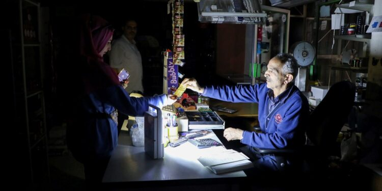 People shop in a grocery store under a portable electric light during a power cut near Bhamdoun, Lebanon, October 9, 2021.