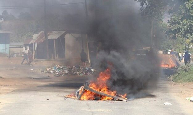 A barricade in the road that is on fire is seen in Mbabane, Eswatini, amid protests.