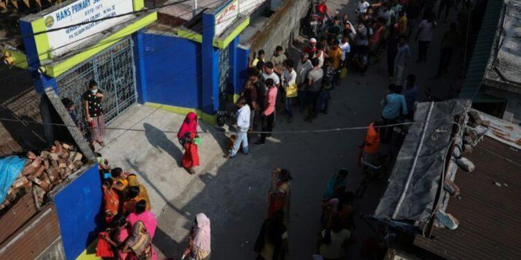 Vigilias de medianoche, colas serpenteantes mientras algunos indios esperan vacunas COVID-19